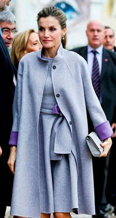 Queen Letizia - Pearl grey Carolina Herrera double-wool coat. Cocoon silohuette with a funnel neck and contrasting purple underside. Matching dress sleevless with an attached self-belt that ties at the front. Vintage vibe - 1950's