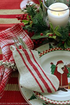 A fantastic tablescape!!!  Love the blending of fabric patterns...   Note the tree in the center plate is around the perimeter of the larger plate...and the silverware is contained in a stocking....  Love it!!