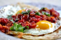 Huevos rancheros recipe with fried eggs served on corn tortillas and smothered in cooked salsa. The best Mexican breakfast ever.