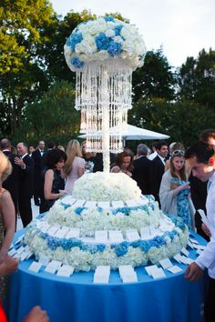 Beautiful blue and white escort card table with tall foral center piece.