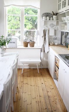 Great wood floor in white kitchen. Lovely window