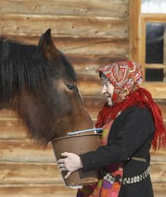 "Galina Konyeva, 74, a member of the singing group ""Buranovskiye Babushki,"" feeds a horse at a folk museum near the village of Ludorvai in the central Russian region of Udmurtia."