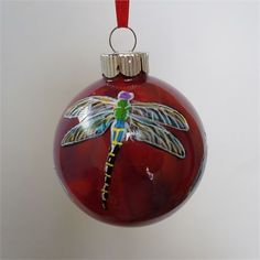 This glass dragonfly ornament is hand painted by me . It has a red, burgundy and deep purple swirled background painted inside the glass ball. The dragonflies are painted one at a time on the outside of the ball. I do not use stencils or decals so each ornament I create is unique. The dragonflies are painted all around ornament. The ornament pictured is the one you will receive. The ornament is signed and painted on a 2 1/2 inch glass ball. (about tennis ball size)   Ornaments can be per...