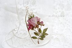 This is a handmade pendant. The heart is made of resin and real roses. Chains to pendant is silver in color with length 26 inches. Size pendant,