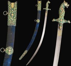 Persian or Indian shamshir, 18th century, signed Asadullah Isdahani, watered steel blade inlaid with gold inscriptive cartouches on each side and on straight edge, the hilt with dark green enamelling and chiselled with gilt relief foliate decoration set with colourful stones, the pommel and quillons in the form of tigers' heads with black enamelled details, the velvet covered scabbard mounted with en-suite decoration near the hilt, at the centre and tip, two hooks for attaching 102cm.