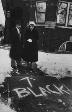 Chicago, 1957: a couple who moved into an all-white neighborhood looking at graffiti in front of their home.