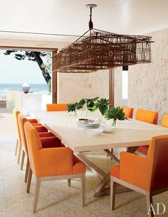 A custom-made light fixture is suspended above a dining table and chairs designed by Atelier AM.