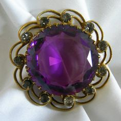 Striking gold tone filigree brooch featuring a large faceted prong set amethyst colored stone surrounded by 11 small stones. Measures 1 1/2 in