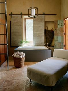 I like the creamy look of this travertine with the soaking tub and the rustic window treatments.  Maculine but very inviting!