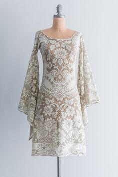 1970s crochet lace dress with long bell sleeves, round neck, and features floral motifs.