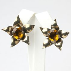 Golden-topaz glass stones are the centers of these Retro Modern sterling silver curled-leaf 1940s earrings.