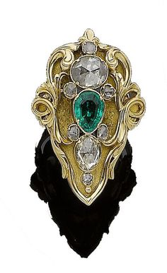 An art nouveau emerald and diamond dress ring, circa 1900 The stylised textured pear-shaped plaque, set with a pear-shaped emerald and graduating rose-cut diamonds in closed-back settings, to scrolling shoulders,