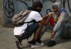 Un manifestante es ayudado por otro durante una manifestación contra el gobierno del presidente de Venezuela, Nicolas Maduro en Caracas.  REUTERS / Carlos Garcia Rawlins