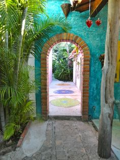 Brick surrounds door with circular mosaics on the terrace on the other side of a turquoise wall