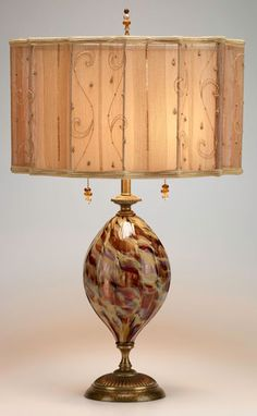 Taylor Table Lamp  kn-kinzig-design-lighting-taylor-table-lamp-85ae74    Ruby, green and gold swirls, on a hand blown glass base, topped with a beautiful round, pleated raw silk shade. Double sockets. Height listed does not include finial. 60-watt maximum bulb. Engraved signature on bottom.