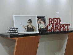 """Para decorar, usei alguns rolos de filmes feitos de papelão, tirei uma foto minha, em homenagem ao filme Bonequinha de luxo, atrás uma foto da Meryl Streep comendo pizza e letras de madeira escrito """"Tapete vrmelho"""", que colei e pintei."""