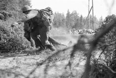 Finnish pioneers retrieving the body of their fallen comrade, while being under…