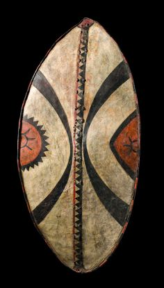 Africa | War shield from the Massai people of Kenya | Cow hide, polychrome paint | Young warriors, not yet considered to be the equals of the older, were allowed just the use of black motifs on their shields. Only a man who had proven his bravery was allowed the colour red