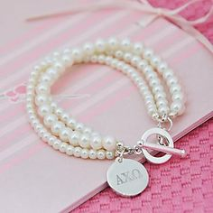 so cute and classic. every sorority girl needs her pearls ΑΧΩ Alpha Chi Omega AXO Lyre Red carnation Denton County Chapter Alumnae Greek Sorority Sigma Alpha Omega, Delta Phi Epsilon, Alpha Sigma Alpha, Chi Omega, Sigma Kappa, Greek Jewelry, Pearl Jewelry, Jewelery, Pearl Bracelet