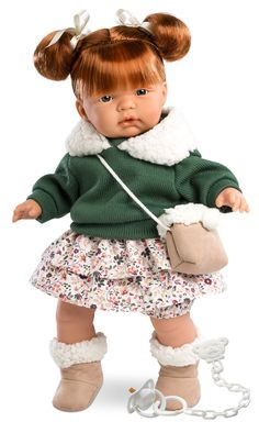 Kate Baby Doll is fashion-ready with her green sweater with fur-lined collar, floral skirt, ugg-like boots and matching purse.  Kate's face is sprinkled with freckles to complement her red hair and green eyes. Kate cries and is able to suck her pacifier to quiet her but the pacifiers and the batteries can be removed if not wanted. The white pacifier is attached to the dolls clothing with an teddy shaped clip. All Llorens dolls are crafted in Spain.