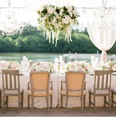 Comments from Studio Emme: This absolutely takes our breath away. Hanging chandeliers of flowers and greens alternating with chandeliers of crystal is a stunning statement above this dining table. You would't even need anything on the table! But we love how they filled it with flowers and candles anyways ; ) Budget $$$+ // Photography: KT Merry Photography - www.ktmerry.com