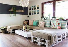 Salon en palette décoré avec des coussins sur parquet marron → touslescanapes.com