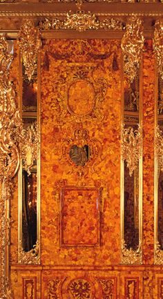 Amber wall panel with gilded woodcarving and mirror pilasters