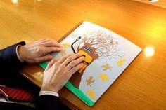 manos de un hombre con discapacidad visual explorando un dibujo en relieve de un árbol y unas hojas