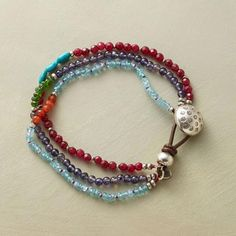 "$98.00 Overlapping strands create an interplay of smooth blue iolites, apatite rondelles, faceted red jade, chrome dioxide, carnelian and turquoise beads. Each strand with a contrasting centerpiece. Leather and sterling silver button clasp. Handmade exclusive. 7-1/4""L."