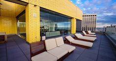 Rooftop terrace at William Beaver house NY: midcentury furniture against yellow brick
