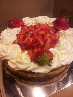Cheesecake with walnut & graham cracker crust and fresh whipped cream and strawberries