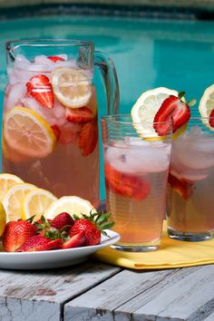 strawberry lemonade flavored water in pitcher and glasses out by the pool