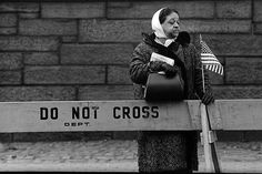 A woman stands behind a police barrier, holding an American flag during the 1965 Selma, Alabama Civil Rights Movement.