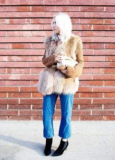 Always Judging blogger rocks girlfriend jeans, a fur vest, and low heeled booties. The perfect shopping outfit, no?