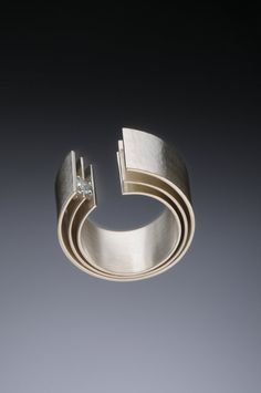The three layers of this unique ring, reminiscent of waves, are connected with invisible rivets at the base. The exterior is finished with a