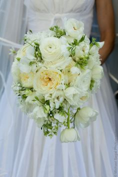 The bridal bouquet will be a cascade bouquet of ivory garden roses, lily of the valley, Queen Anne's lace, blush pink ranunculus, ivory spray roses, and gray dusty miller wrapped in champagne ribbon with the stems showing.