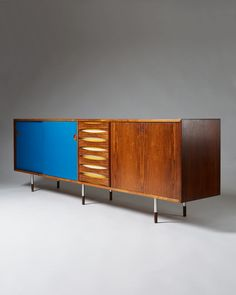 """""""Credenza"""" model 29A designed by Arne Vodder for Sibast, Denmark. 1958-1959. Freestanding Brazilian rosewood sideboard on six round steel legs with rosewood shoes. Front with two reversible sliding doors with respectively rosewood and original blue paint. Middle section with seven drawers with curving handles and alternating white/yellow paint. Bar section with fold-down front, inside covered with black formica. Back fully veneered in rosewood."""