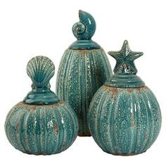 "Set of three weathered ceramic jars with decorative seashell toppers.Product: Small, medium and large jarConstruction Material: CeramicColor: BlueFeatures: Seashell tops Dimensions:  13.75"" H x 6.5"" Diameter (large)"