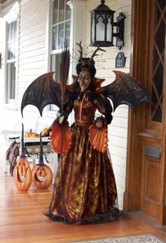 This beautifully designed life-size witch features an orange spider web gown and an amazing wing span! A pet spider resides on her head :)