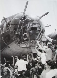 "American crowds greet the B-17 ""Memphis Belle"" on its war bond fundraising tour. It was the first B-17 to complete 25 missions over Europe."
