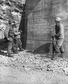 United Nations soldiers read propaganda written, in English, by Communist forces, on a wall near an underpass during the Korean War, Korea. Two of the men hold cameras. The message urges the United Nations forces not to 'die for Wall Street,' and to give up the battle and return home.