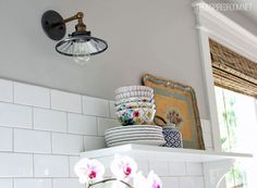 Kitchen details... sconce + colorful stacked bowls on shelf + bamboo shade.  Lots more photos of this pretty kitchen makeover.