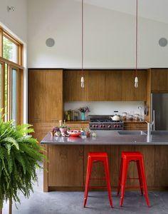 Com detalhes em vermelho, como as cadeiras Tolix e o fio das lâmpadas pendentes, o décor é sóbrio e combina com o restante da residência, erguida em um terreno que antes abrigava uma casa de fazenda deteriorada.  Fotografia: Revor Tondro/ The New York Times.