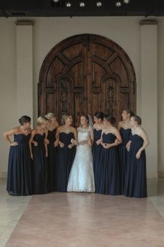 Bride & bridesmaids in front of a large, old wooden door- Elegant summer wedding - Christine Gosch