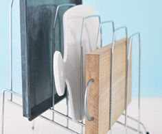 Cookie sheets can be organized and sorted by size using a vertical file holder. These file holders are slanted and sorted by size from small to large going up. The cookie sheets are placed in the file slots and easily identified without the need to move each pan to find the right one.