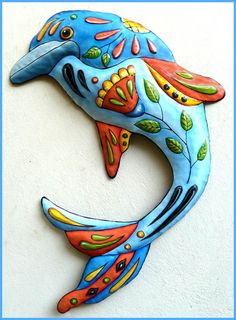 """Hand Painted Metal Blue Dolphin Wall Hanging - Nautical Decor - Poolside Decor - Tropical wall art, Nautical decor - Hand painted metal dolphin measures 32"""" x 24"""". Great decor for the pool area or out on the patio. Hand cut from recycled steel drums in Haiti. This is not a flat piece. The features and body have been pounded out to give the dolphin a rounded look."""