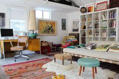 Ugh I LOVE this eclectic living room! The modular book shelf, boho rug, little mid century modern turquoise stool, sheepskin rug, and various colors.