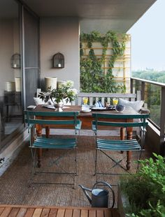 Eclectic Dining Area ~ Small slatted chairs aren't too stuffy for a small balcony. ~ Pair pieces with different styles for a setting that looks inviting and charming as opposed to straight-from-the-showroom-floor. Eschew flimsy plastic tables and chairs for handsome wooden and metal and ceramic pieces, too. Here, a vintage teak bench, authentic Parisian park chairs and an antique Quebec farmhouse table add old world style and French country comfort.