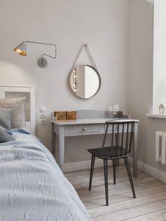 szary kinkiet nowoczesny , okrągłe lustro na rzemyku,szara toaletka z grafitowym krzesłaem w sypialni z białym łóżkiem - Lovingit.pl