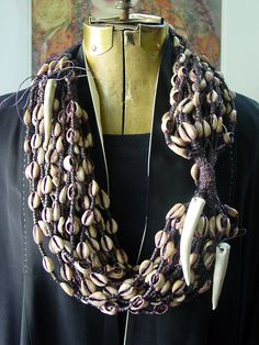 Necklace | Designer ?. A vintage piece sourced in Africa; 20 strands of macrame fibers and cowries shells. The 3 antler tines are new additions to this original piece.